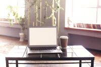 Photo of white blank screen of laptop with keyboard lying on wooden little table with cup of coffee