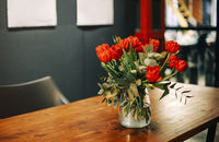 Bunch of fresh red tulips in glass vase on wooden table in living room