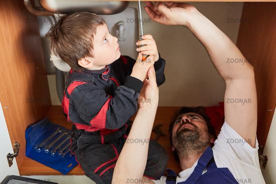 Junge hilft seinem Vater als Heimwerker