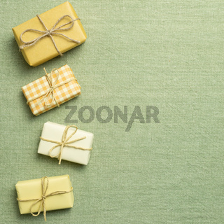 Yellow gift boxes on green fabric background. flat lay, top view, copy space