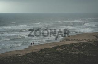 Couple walking on foggy beach along stormy ocean in Daimus, Spain