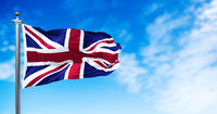 The national flag of the United Kingdom flying in the wind. Outdoors and sky in the background.