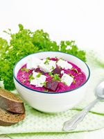 Soup puree of beetroot with feta in bowl on white board