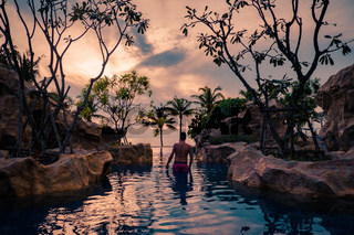 Luxury swimming pool in tropical resort, relaxing holidays in Thailand. , Young man during sunset by swimpool in Pattaya