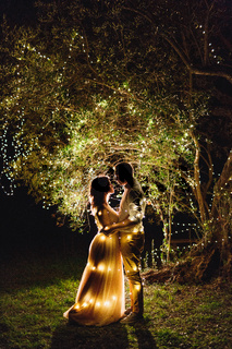 Standing man hugs woman in a beautiful dress on a background of a tree hung with glowing bulbs