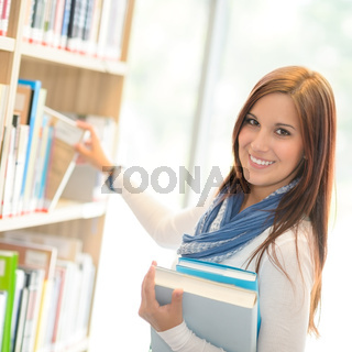 Happy student choosing books from library shelf