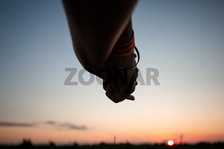 Romantic couple holding hands in summer field at sunset