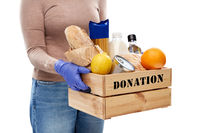 woman in gloves with food donation in wooden box