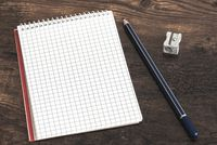 spiral notepad, pencil and sharpener on table