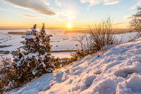 Beautiful sunset over snowy winter landscape in the Swabian Alps with trees in the foreground