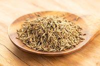 Cumin seeds on wooden spoon on table. Cuminum cyminum