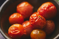 Roasted cherry Tomatoes placed in a ceramic dark bowl. Close up macro shot.