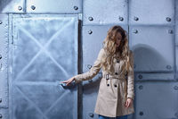 Portrait of young blonde female with long hair in beige cloak on metal wall background.