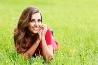 Smiling woman laying on grass