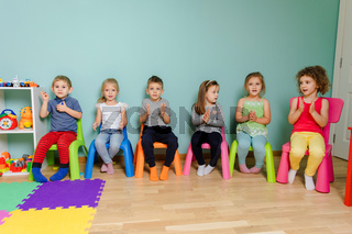 Kids are sitting on the colorful chairs, clapping hand