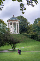 A couple is walking in the English Garden to watch the famous architecture of the Monopteros in the autumnal season.