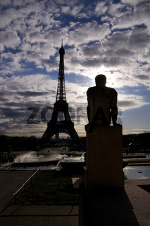 Backlit silhouette of Eiffel Tower and statue on Trocadero in Paris