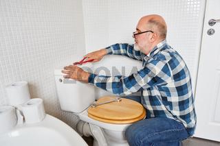 Handwerker montiert den Spülkasten vom WC