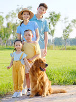 Happy family of four and pet dog in the park