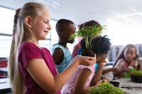 Caucasian girl smiling while holding a plant seedling in the class at school
