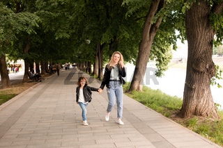 The mom and little girl walk around the city are holding hands