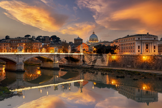 View of the Tiber River and Saint Peter's Basilica at sunset in Rome Italy
