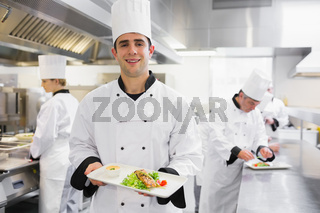 Happy chef holding salmon dish