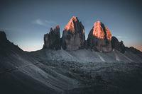 Three peaks of Lavaredo (Drei Zinnen or Tre Cime di Lavaredo) in the Sexten Dolomites National Park during sunrise with light on the peaks
