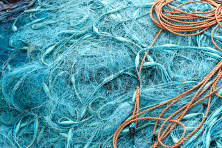 Knäuel aus blauem Fischernetz und orangenem Seil