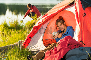Camping girl in tent drinking from pot
