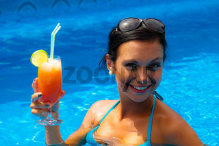 Frau mit Cocktail im Pool