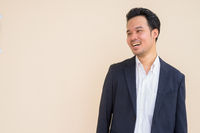 Portrait of Asian businessman wearing suit against plain background while smiling and thinking