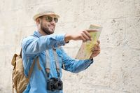 Handsome tourist man look at map while pointing finger in the direction of destination. Travel concept. Trip, backpacker tourist.