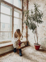 Pensive young woman sitting on windowsill with vintage camera in hand in room of abandoned house