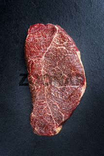 Traditional dry aged raw loin of a horse steak natural offered as top view on a black board with copy space