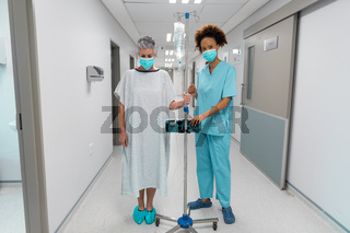 Caucasian female patient wearing face mask standing on corridor with drip bag and talking to doctor