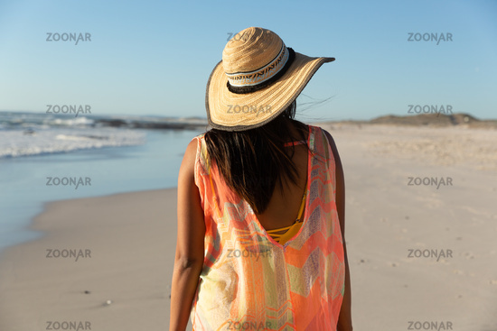 Happy mixed race woman on beach holiday looking away