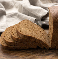 sliced baked rectangular rye flour bread on brown board, healthy food
