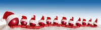 rote Christbaumkugeln mit Weihnachtsmützen im Schnee