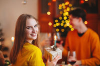 Happy smiling blond woman giving wrapped gift to friend while sitting at table