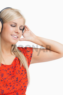 Smiling woman in orange dress listening to music