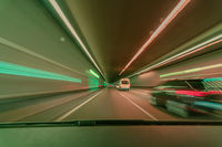 Highspeed blurred background, driving fast through a tunnel overtaking a car with light blurry long exposure effects