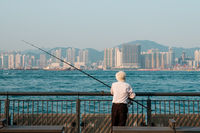 fiaher man with fisher rod on waterside with skyscraper skyline background, Hong Kong -