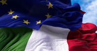 The national flag of Italy waving in the wind together with the European Union flag blurred in the foreground