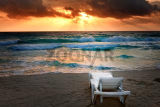 Empty beach chair before sea. Bright sunset