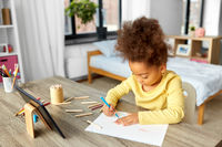 little girl drawing with coloring pencils at home