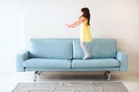 Little caucasian cute girl in yellow dress playing and jumping on blue sofa in living room at home