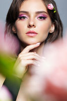 Beauty portrait of young woman with front bokeh of pink flower petals.