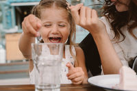 Little girl with mom playing with ice cubes in a cozy cafe.