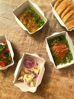 Assorted fresh dishes in separate disposable small paper boxes on wooden table